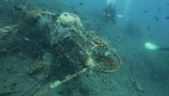 Scuba divers exploring airplane wreck covered in marine life Stock Footage