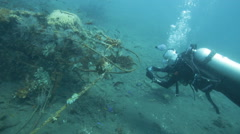 Scuba diver photographing airplane wreck underwater Stock Footage