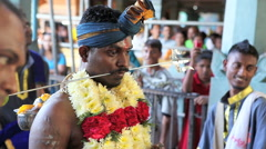 Devotee with pierced cheeks at Batu Caves temple during Thaipusam Hindu Festival Stock Footage