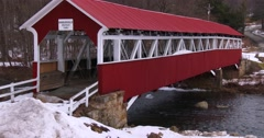 A pretty red covered bridge over a river in winter. - stock footage