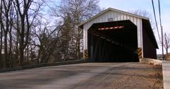 An Amish horse cart travels through a covered bridge along a road in rural Stock Footage