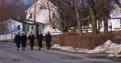 Amish girls walk along a road in rural Pennsylvania. Stock Footage