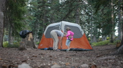 Mother and daughter staking down a tent Stock Footage