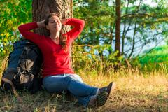 strongly weary backpacker resting against a tree - stock photo