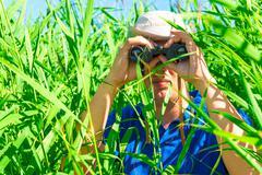 man in an ambush the reeds with binoculars - stock photo