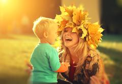 young beautiful mother playing with her little son in an autumn park. - stock photo