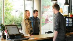Young couple (man and woman) enter to the building (coffee) -order at the bar Stock Footage