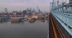A commuter train crosses the Ben Franklin Bridge with Philadelphia, PA in Stock Footage