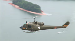 Huey gunship flies over water with Kiowa helicopter not far behind Stock Footage