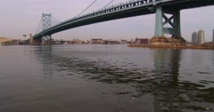 Tilt up to the Ben Franklin Bridge leading to Philadelphia, PA. - stock footage
