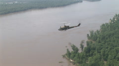 Huey helicopter gunship flies over waterway Stock Footage