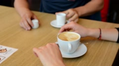 Young couple sit (man and woman) at the table with coffee - shot only on hands - stock footage