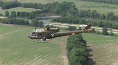 Huey helicopter gunship flies near highway Stock Footage