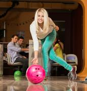 Stock Photo of people watching young blond woman throwing bowling ball