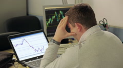 Financial trader looking at stock market graphs on laptop, working overtime. - stock footage