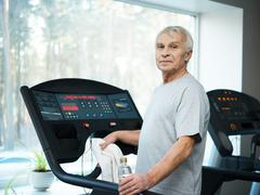 Tired senior man on a treadmill with towel and bottle of water Stock Photos