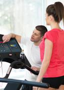 Trainer explains to a young woman how to use treadmill in fitness club Stock Photos