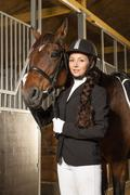 beautiful girl with her horse in a stall - stock photo