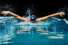 Stock Photo of young woman in blue cap and swimming suit in pool