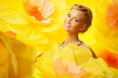 beautiful young cheerful blond woman in colourful dress among big yellow flow - stock photo