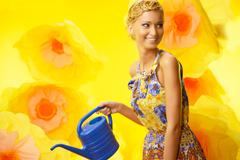 beautiful young cheerful blond woman in colorful dress among big yellow flowe - stock photo