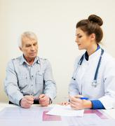 senior man at doctors's office appointment with pills - stock photo