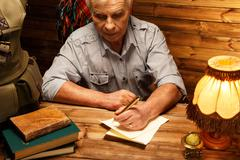 senior writing letter with quill pen in homely wooden interior - stock photo