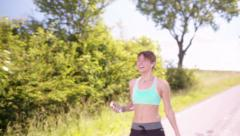 Victorious Runner, girl running on the road, running outside Stock Footage