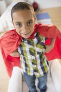 Mixed race boy wearing cape on armchair Stock Photos