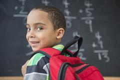 Mixed race boy doing math problems at board in class Stock Photos