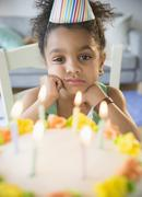 African American girl pouting at birthday cake Stock Photos