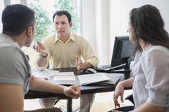 Hispanic businessman talking to clients in office Stock Photos