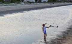 Caucasian girl fishing with net on beach Stock Photos