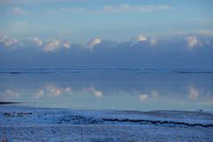 Clouds reflected in still ocean in arctic landscape Stock Photos