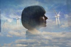Double exposure of businesswoman and wind turbines in clouds Stock Photos
