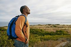 Black man overlooking rural hillside Stock Photos