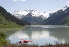 Seaplane docked in still lake in mountain landscape, Anchorage, Alaska, Denali Stock Photos