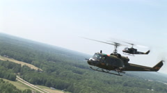 Huey gunship and medivac fly together Stock Footage