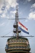 Flag flying from pirate ship against blue sky Stock Photos