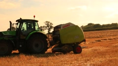 Tractor preparing hay bales on a wagon Stock Footage