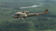 Huey gunship in the air from the air Stock Footage