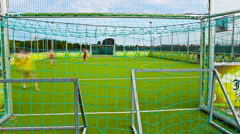 time lapse small football soccer in the small grass court ,kids playing game - stock footage