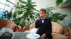 Boy 7 years in a suit sitting in a chair eating ice cream Stock Footage