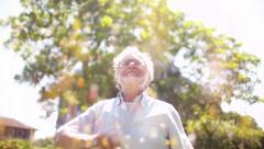 Older man enjoying Confetti, Man throwing confetti in the air  - stock footage