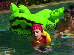 Boy pulling his mother on toy in the swimming pool, slow motion shot Stock Footage