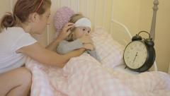 Little girl sick in bed with mother checking time Stock Footage