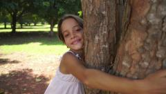 9of18 Happy school girl hugging tree in park, ecology, people - stock footage