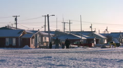 People walk along a snowy road at Churchill, Manitoba, Canada, Hudson Bay. - stock footage