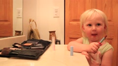 Two year old applies lipstick Stock Footage