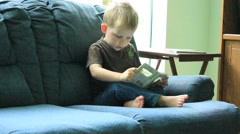 Preschool boy sits on couch and reads Stock Footage